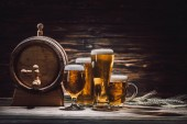 Fotografie beer in glasses, wheat spikelets and beer barrel on wooden table, oktoberfest concept