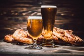 two glasses of fresh beer and tasty pretzels on wooden table, oktoberfest concept