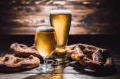 two glasses of beer and delicious pretzels on wooden table, oktoberfest concept