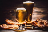 two glasses of beer and tasty pretzels on wooden table, oktoberfest concept