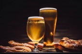 glasses of beer and tasty pretzels on wooden table, oktoberfest concept