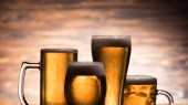 Photo four glasses of golden fresh beer on wooden background, oktoberfest concept