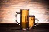 Fotografie pivo ve dvě sklenice na dřevěný stůl, oktoberfest koncepce