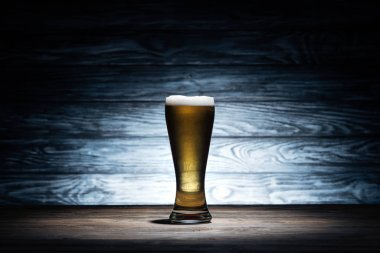 glass of tasty beer with foam on wooden table, oktoberfest concept