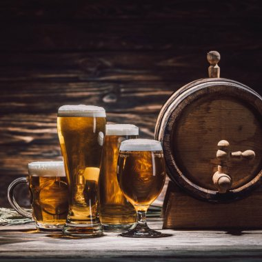 fresh beer in glasses and beer barrel on wooden table, oktoberfest concept