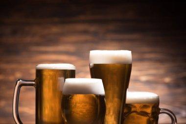 Four glasses of tasty beer on wooden background, oktoberfest concept stock vector
