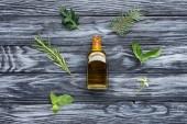 Fényképek emelt szintű megtekintése üveg természetes növényi illóolaj és a zöld levelek, a fa felülettel