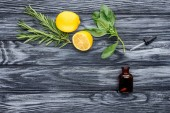 Photo elevated view of bottle of natural herbal essential oil, dropper and lemons on wooden table