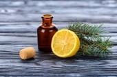 Fényképek üveg természetes növényi illóolaj, fenyő gallyak, citrom és parafa felület