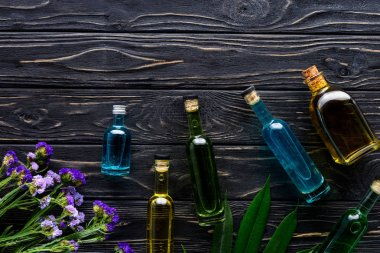 colored bottles of natural herbal essential oils and violet flowers on wooden surface