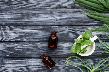 top view of two bottles of natural herbal essential oils and green herbs on wooden table