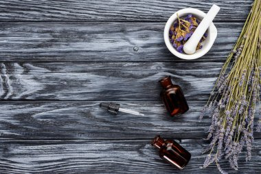 top view of bottles of natural herbal essential oils, dropper and dried flowers on wooden table