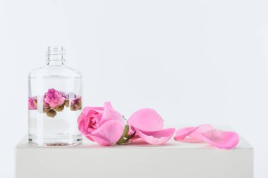 bottle of aromatic essential oil with pink roses on white surface