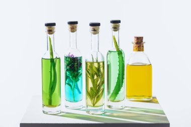 bottles of aromatic essential green and yellow oils with herbs on white cube