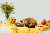 Fotografie close up view of cooked festive turkey on baking pan, glasses of wine and pumpkins on surface with tablecloth on grey background, thanksgiving holiday concept