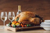 Fotografie close up view of traditional roasted turkey, vegetables and glasses of wine for thanksgiving dinner