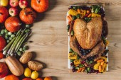 Fotografie top view of roasted turkey and vegetables for thanksgiving traditional dinner on wooden tabletop
