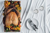 Fotografie flat lay with roasted turkey, vegetables and glasses of wine for thanksgiving holiday dinner on tabletop