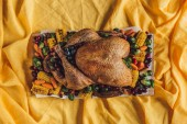 Fotografie top view of roasted festive turkey and vegetables on tabletop with yellow tablecloth, thanksgiving holiday concept