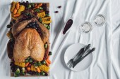 flat lay with roasted turkey, vegetables and glasses of wine for thanksgiving holiday dinner on tabletop