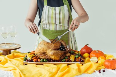 partial view of woman in apron cutting roasted turkey for thanksgiving holiday dinner on grey background