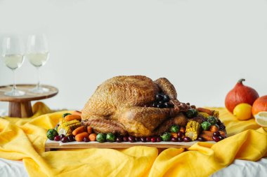 Close up view of festive thanksgiving dinner table set with glasses of wine, roasted turkey and vegetables on tabletop with tablecloth stock vector