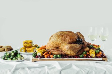 close up view of holiday dinner table set with roasted turkey, vegetables and glasses of wine on grey background, thanksgiving holiday concept