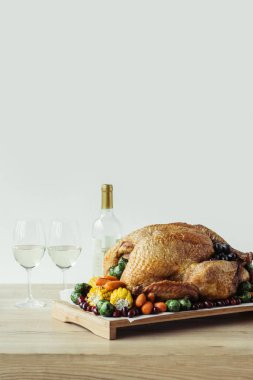 close up view of festive thanksgiving dinner table set with glasses of wine, roasted turkey and vegetables on wooden tabletop on grey backdrop