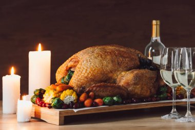 close up view of candles, traditional roasted turkey, vegetables and glasses of wine for thanksgiving dinner on wooden tabletop