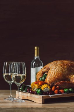 close up view of traditional roasted turkey, vegetables and glasses of wine for thanksgiving dinner