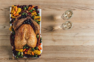 top view of roasted turkey, vegetables and glasses of wine for thanksgiving traditional dinner on wooden tabletop