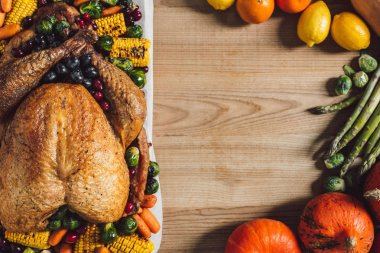 flat lay with fresh vegetables and festive turkey arranged on wooden surface, thanksgiving holiday concept