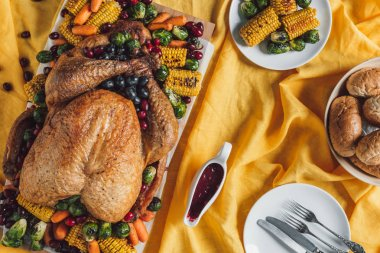 flat lay with roasted turkey, vegetables and sauce for thanksgiving holiday dinner on tabletop