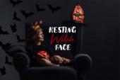 Fotografia bambino adorabile in costume di halloween che riposa in poltrona in camera oscura con la scritta strega fronte di riposo
