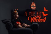 Photo adorable kid in halloween costume resting in armchair in dark room with a wee bit wicked lettering