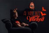 Fotografie Rozkošné dítě v halloween kostýmu odpočinku v křesle v temné místnosti s nápisem trochu zlý