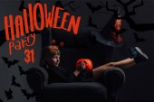 Rozkošné dítě v halloween kostýmu odpočívá v křesle v temné místnosti s halloween party 31 nápisy