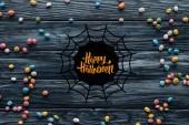 pohled přehledné barevné lahodné bonbóny na dřevěné pozadí s pavučina a nápis happy halloween
