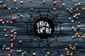 pohled přehledné barevné lahodné bonbóny na dřevěné pozadí s pavučina a Koledu nebo vám něco nápisy