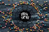 circle made of colorful delicious candies on wooden background with spider web and trick or treat lettering