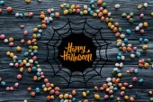 circle made of colorful delicious candies on wooden background with spider web and happy halloween lettering