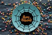 top view of plate with spider web and happy halloween lettering surrounded by colorful candies on wooden table