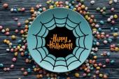 Fotografie pohled shora desky s pavučina a nápis happy halloween obklopené barevné bonbóny na dřevěný stůl