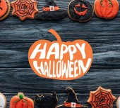 top view of arranged halloween homemade cookies placed in rows on wooden background with pumpkin and happy halloween lettering