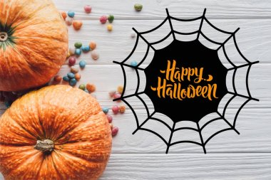 top view of pumpkins and colorful candies on wooden background with spider web and