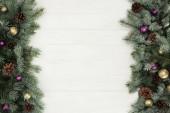 Fotografie krásná jedle stálezelených větviček, lesklé cetky a šišky na bílém pozadí dřevěná