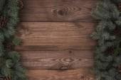 pohled shora stálezelených jehličnatých větví s šišky na dřevěné pozadí