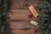 pohled shora na vánoční dárky, lesklé cetky a jehličnaté větve s šišky na dřevěné pozadí