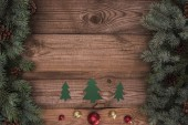 pohled shora zelené knihy jedle s lesklé cetky a jehličnaté větve s šišky na dřevěný povrch, Vánoční pozadí
