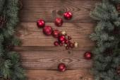 pohled shora lesklé červené a zlaté ozdoby a jehličnaté větve s šišky, Vánoční pozadí